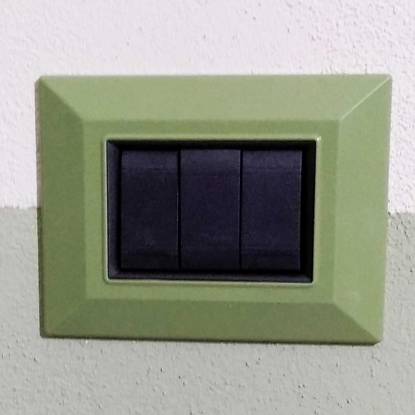 placca compatibile verde menta montata a muro tasti neri anello nero